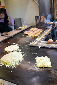 our dinner of okonomiyaki in Namba, Osaka at Ajinoya - you usually have it prepared either by the chef or you make it yourself at the table. At Ajinoya it is made by the chef and if you sit at a booth they then bring it to your own grill where you can top it as you wish