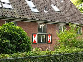 De stalen luiken die voor de ramen werden gehangen werden gecamoufleerd als Hollandse boerderij luiken.