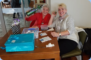 Our intrepid Door Staff, Delyse Whorwood and Margaret Black, showing off the three lovely raffle prizes on offer.