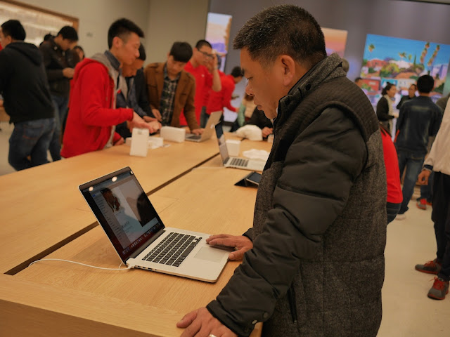 customer using a laptop for sale at the SM Lifestyle Center Apple Store in Xiamen, China