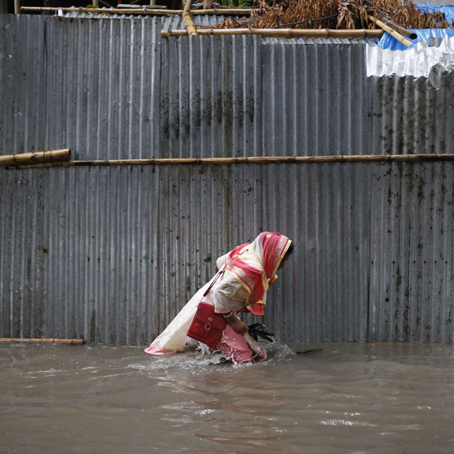 A woman trudges through floodwaters. Photo: Teen Vogue
