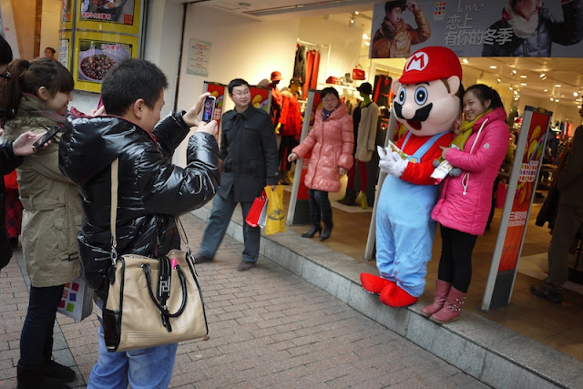 young woman having her photograph taken with a Mario mascot in Changsha, China