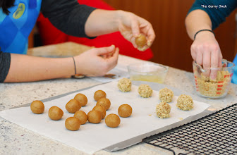 Photo: Once we finished with the appetizers, it was time to starting baking cookies. Our first cookies we made as teams and they were called Gingerbread-Turtle Thumbprint Cookies. Shawn and Jocelyn rolled their gingerbread cookie dough balls in chopped walnuts.