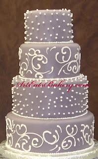Four tier purple fondant wedding cake with white royal icing curlicues and edible pearls