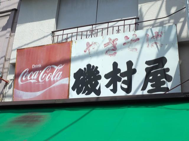 コカ・コーラの赤い看板の横に書かれた「やきそば磯村屋」の文字