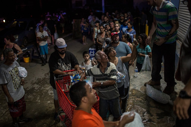 A long line forms to buy ice in Arecibo, Puerto Rico, at 6:56 p.m. on 27 September 2017. Photo: Kirsten Luce / The New York Times