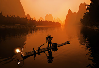 """Photo: The Morning Fisherman (The Li River)  Now, getting to this place was not easy!  I arrived about 1 AM at a tiny family-run inn by the river. I was meeting a local guide at 5 AM, so I didn't get a lot of what I would call """"quality sleep"""". Anyway, I got up very early and went downstairs in pitch black. There seemed to be a big white cloth box I had to go around to find the front door. My guide was outside. The door was locked and we could not figure out how to get it open. Everyone at the little inn was sound asleep and I was totally confused. Then, from inside the big white box, a body flew out of it! There was a 60-year-old Chinese guy inside that was sleeping until I woke him up with all my lock-manipulations. His naked limbs in the white sheets scared the bejeezus out of me and woke me right up!  And then we were on the river about 5:15. It was still completely dark outside. And I mean COMPLETELY DARK. It was a thin bamboo raft with an outboard motor.    from Trey Ratcliff at www.stuckincustoms.com"""