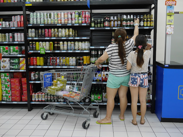 two young women, one wearing shirts with a U.S. flag design, selecting a German beer from a selection in Walmart