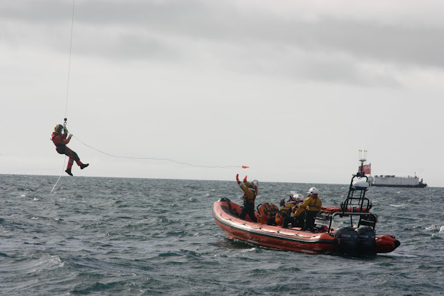 9 October 2011. Winchman from the Coastguard helicopter despatches a 'short' hi-line to a waiting crew member of Poole ILB during a training exercise. Photo: Poole RNLI/Ade