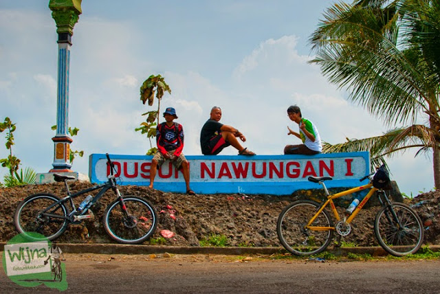 Para pesepeda beristirahat di tugu Dusun Nawungan I dalam perjalanan menuju Gua Lawa yang ada di Dusun Nogosari, Selopamioro, Imogiri, Bantul, Yogyakarta