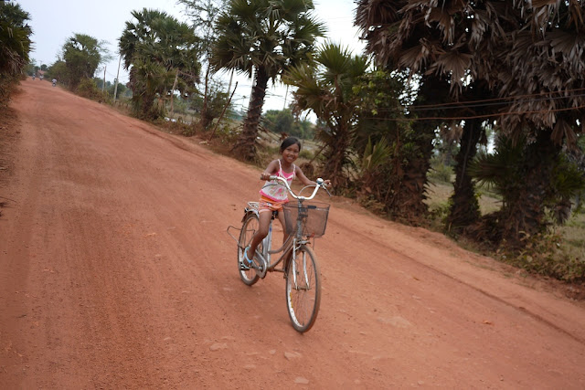 girl riding a bike on a dirt road
