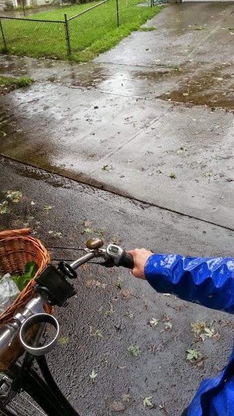 DarkEm in a blue rain slicker riding a bike on a rainy street
