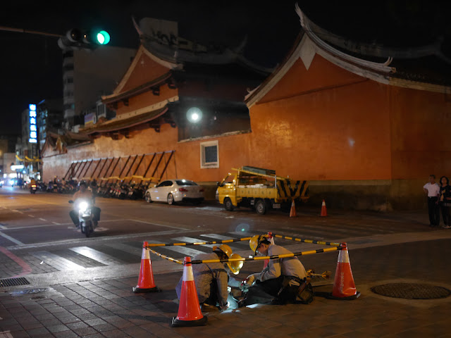 three workers looking into a utility hole at night next to the Sacrificial Rites Martial Temple (祀典武廟) in Tainan, Taiwan