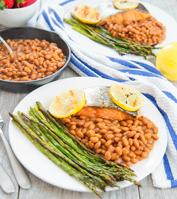 close-up photo of a plate with Brown Sugar Glazed Salmon, baked beans, and roasted asparagus