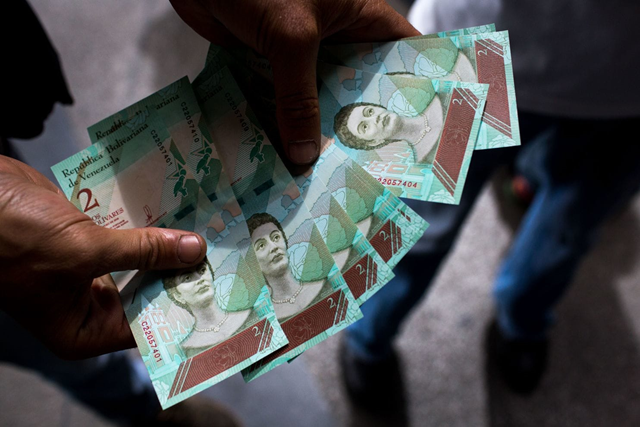 A man displays new 2 sovereign bolivar banknotes in Caracas on 21 August 2018. Venezuelans on Tuesday began confronting a currency devaluation and new economic measures that many feared could make the situation worse. Photo: Manaure Quintero / Bloomberg