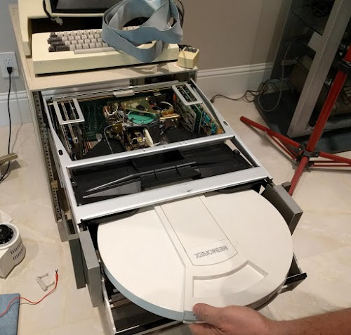A disk cartridge is inserted into the Alto's drive. The drive has been pulled out and the cover removed, revealing its internals.