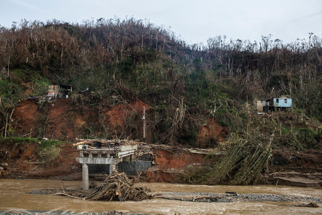On the west bank of the Vivi River, in Utuado, Puerto Rico, the remaining chunk of a bridge washed away by Hurricane Maria juts violently and jaggedly, 27 September 2017. Photo: Kirsten Luce / The New York Times