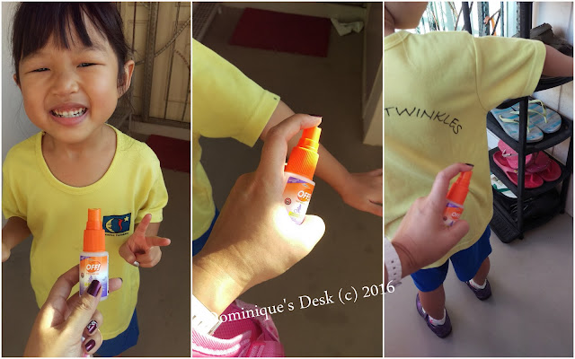 Spraying Tiger girl with insect repellent before she leaves for school