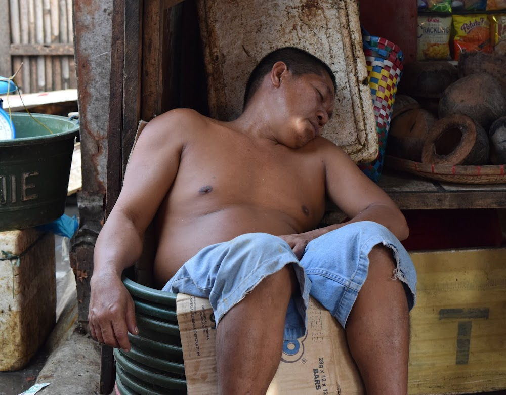 in the market, this guy sleeping in a bucket!!!  hahaha!  His giggling friends motioned for me to photo him....