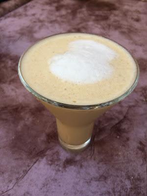 Et høyt, traktformet glass med kaffe med melk.