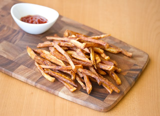 photo of french fries on a board with a bowl of ketchup