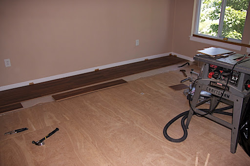 Beginning to put down the hardwood laminate flooring.