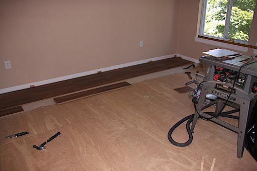 Beginning to put down the hardwood laminate flooring.