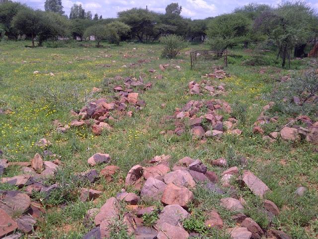 Graveyard in Mochudi, few headstones, just rocks to mark the grave