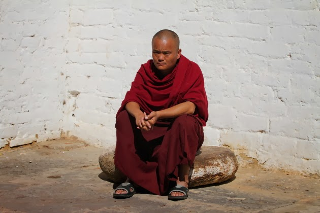 Buddhist monk soaking in the morning sun at Trongsa Dzong, Bhutan