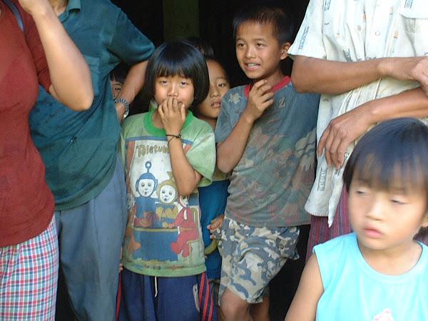 Les enfants du village jouent à cache-cache avec l'appareil photo, c'est une occasion de plus de rire. Malgré qu'ils habitent encore dans des villages retranchés, les enfants doivent impérativement aller à l'école, c'est la condition pour que les habitants de ces villages éloignés de la civilisation, profitent des avantages d'avoir la nationalité thaïe.