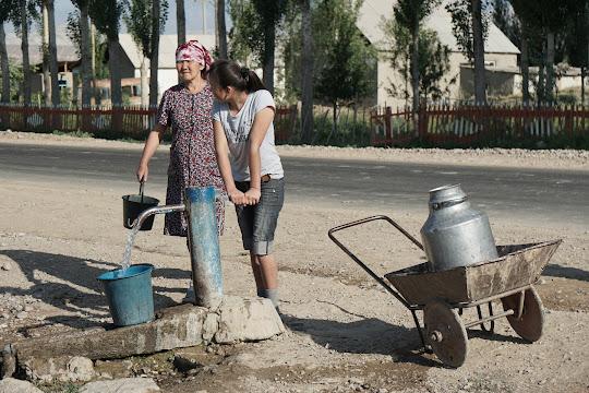 An einer Pumpe neben der Dorfstraße versorgt sich eine Frau mit Wasser