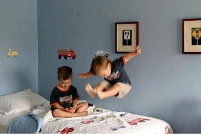 dua anak bermain di atas tempat tidur di kamarnya
