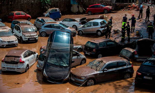 Emergency workers among damaged vehicles in a open parking area of northern Athens after a flash flood struck the Greek capital on 26 July 2018. Photo: Angelos Tzortzinis / AFP / Getty Images