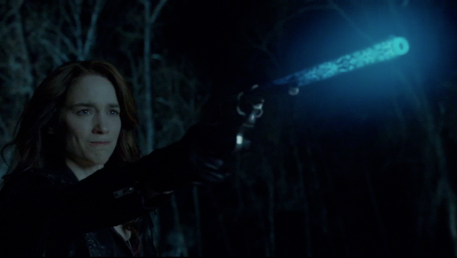 image of Wynonna holding Peacemaker that has glowing blue symbols