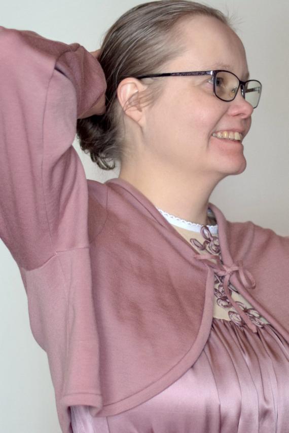Kuvassa on naisen sivuprofiili. Nainen käyttää roosaa merinovillasta tehtyä isoäidin aikaista lukunuttua.