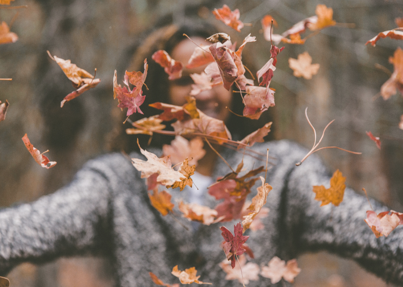 Lady trowing up fallen leaves in a post about five simple ways to feel cosy this Autumn.