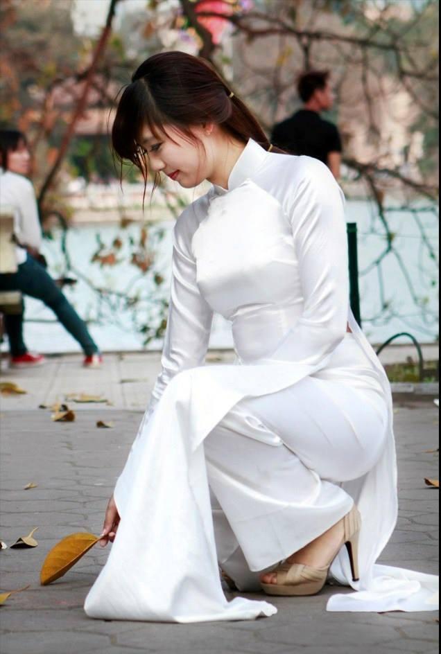 Em mặc áo dài trắng nhặt chiếc lá vàng rơi