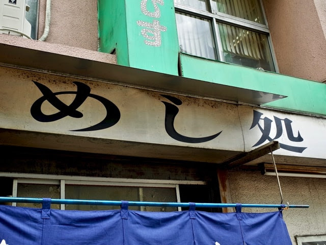 店頭のに書かれた「めし処」の文字