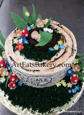 Woodlands baby shower cake tree stump with edible baby topper, flowers, leaves and mushrooms