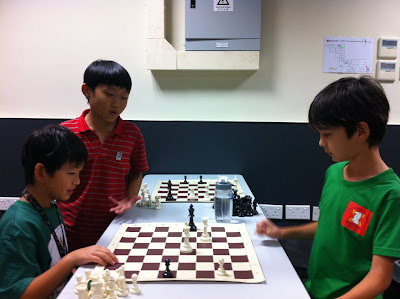 Miguel Angel play simultaneous chess against Jonathan and Bryant