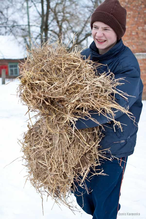Воспитанник Ветринской школы-интерната несет охапку сена что бы поджечь чучело Масленницы и