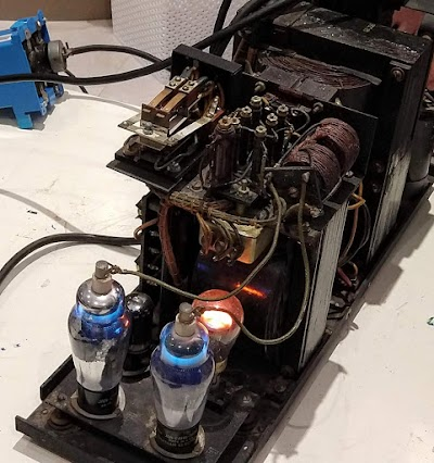 REC-30 Teletype power supply, showing the thyratron tubes with their blue glow and the neon bulb voltage reference glowing orange. The timer/relay is visible in the upper left.