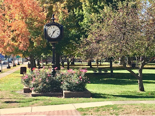 4 sided clock at Carl Fast Park in Jonesville Michigan with trees in full Fall colors
