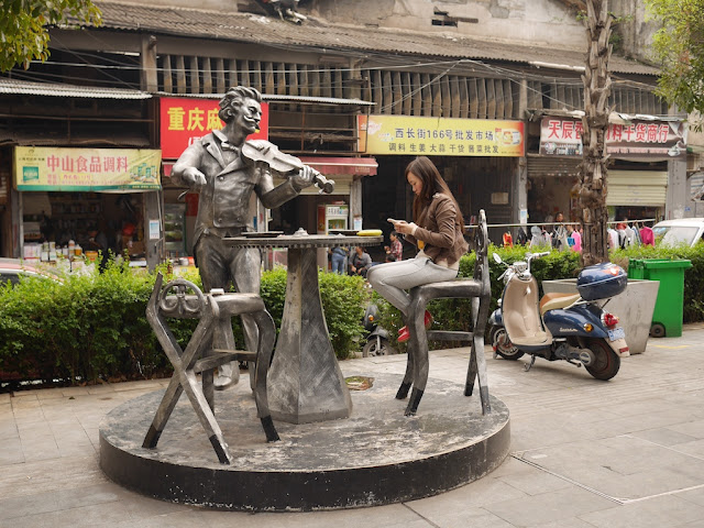female looking at her mobile phone while sitting on a sculpture of chairs and a serenading violinist in Changsha
