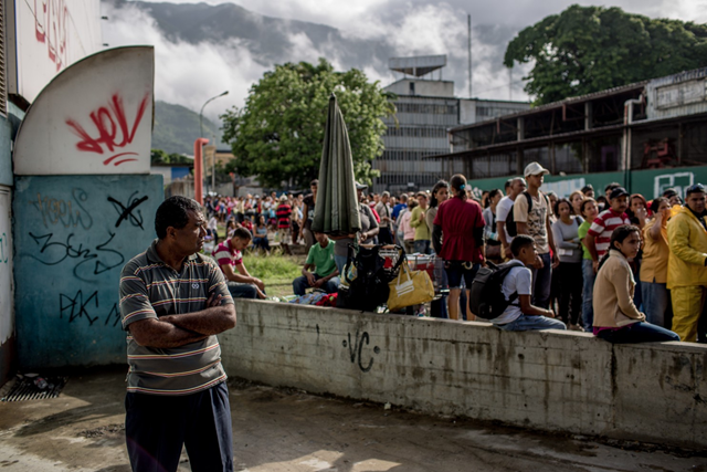 A man waits to buy food at a grocery store in La Urbina, east Caracas, on 22 June 2016. Some people in line arrived at 3 a.m. and waited several hours before being able to make any purchases. Photo: Alejandro Cegarra / Washington Post