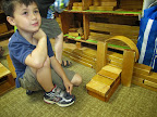 Child builds a symmetrical structure with wooden unit blocks.