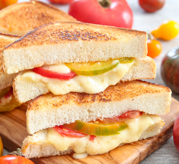 two grilled cheese and tomato sandwiches stacked on a cutting board