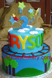 Two tier blue fondant kid's 2nd birthday cake with mountains, trees, the birthday boy's name, and stars