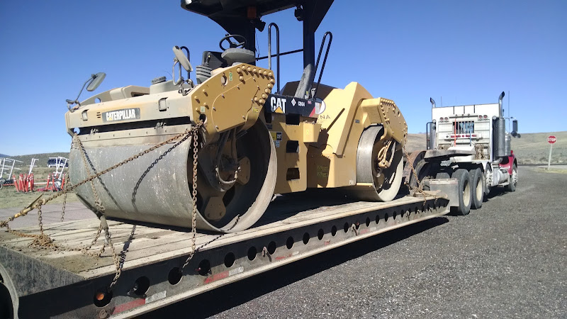 small CAT steamroller chained to flatbed trailer