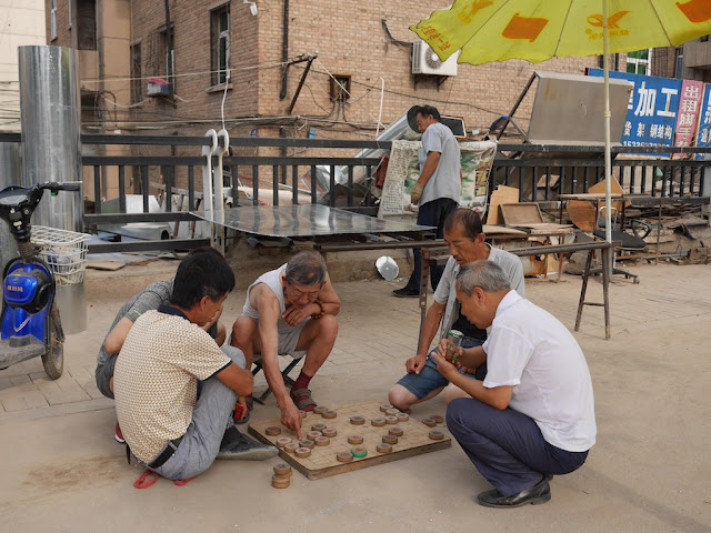 man pointing at a game piece in a xiangqi game on a board sitting on the ground surrounded by 5 men